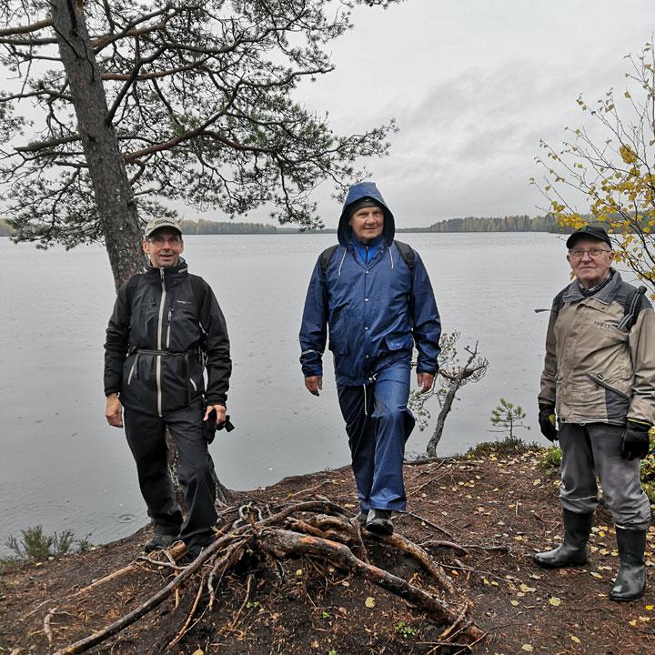 Reippaat patikoitsijat järven rannalla.